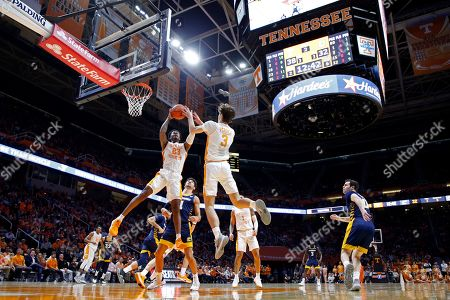 Tennessee guard Jordan Bowden (23) and forward Drew Pember (3) battle for a rebound in front of Chattanooga guard Jonathan Scott (1) during the second half of an NCAA college basketball game, in Knoxville, Tenn