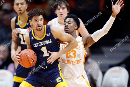 Chattanooga guard Jonathan Scott (1) works for a shot as he's defended by Tennessee guard Jordan Bowden (23) during the second half of an NCAA college basketball game, in Knoxville, Tenn