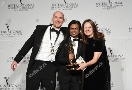 "Stock Picture of James Watkins, Nawazuddin Siddiqui, Dixie Linder. Executive producer/director/writer James Watkins, left, actor Nawazuddin Siddiqui and executive producer Dixie Linder pose with the best drama series award for ""McMafia"" during the 47th International Emmy Awards gala at the Hilton New York, in New York"