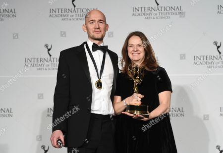"James Watkins, Dixie Linder. Executive producer/director/writer James Watkins, left, and executive producer Dixie Linder pose with the best drama series award for ""McMafia"" during the 47th International Emmy Awards gala at the Hilton New York, in New York"