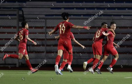 Indonesia's Ardiles Osvaldo Haay, right, celebrates with teammates after scoring a goal during their football match against Thailand at the 30th South East Asian Games in Manila, Philippines on . The Philippines is hosting the SEA games which officially starts Nov. 30 - Dec. 11