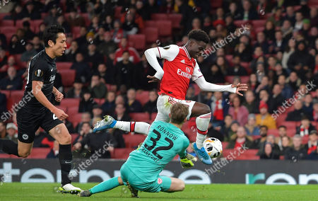 Bukayo Saka of Arsenal leaps the challenge of Frederik Ronnow of Eintracht Frankfurt