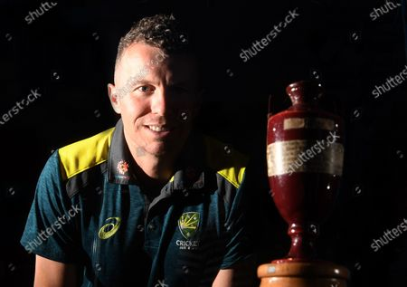 Stock Photo of Australian Test cricketer Peter Siddle poses next to the original Ashes urn during the 'Velvet, Iron, Ashes' exhibition at the State Library Victoria in Melbourne, Victoria, Australia, 26 November 2019. The State Library of Victoria is hosting the 'Velvet, Iron, Ashes' exhibition, with the original Ashes urn on show from 26 November 2019 to 23 February 2020.