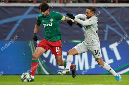 Leverkusen's Karim Bellarabi, right, fights for the ball with Lokomotiv's Vedran Corluka during the Champions League Group D soccer match between Lokomotiv Moscow and Leverkusen at the Lokomotiv Stadium in Moscow, Russia