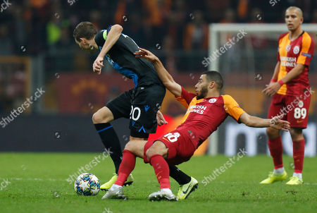 Galatasaray's Younes Belhanda, front, fights for the ball with Brugge's Hans Vanaken during the Champions League group A soccer match between Galatasaray and Club Brugge in Istanbul
