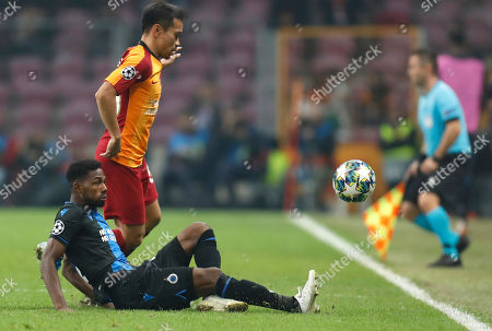 Galatasaray's Yuto Nagatomo, rear, fights for the ball with Brugge's Emmanuel Dennis during the Champions League group A soccer match between Galatasaray and Club Brugge in Istanbul