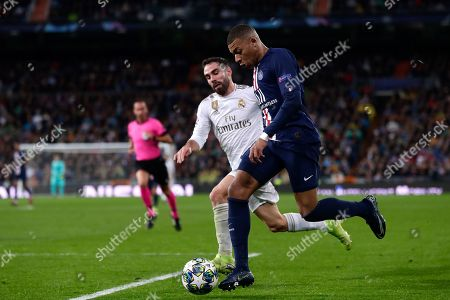PSG's Kylian Mbappe, right, fights for the ball with Real Madrid's Dani Carvajal during a Champions League soccer match Group A between Real Madrid and Paris Saint Germain at the Santiago Bernabeu stadium in Madrid, Spain