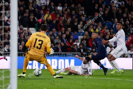 PSG's Kylian Mbappe, second right, attempts a shot at goal in front of Real Madrid's Dani Carvajal, second left, and Real Madrid's goalkeeper Thibaut Courtois during a Champions League soccer match Group A between Real Madrid and Paris Saint Germain at the Santiago Bernabeu stadium in Madrid, Spain
