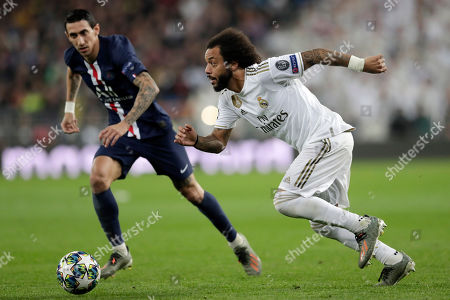 Real Madrid's Marcelo runs with the ball with PSG's Angel Di Maria during a Champions League soccer match Group A between Real Madrid and Paris Saint Germain at the Santiago Bernabeu stadium in Madrid, Spain