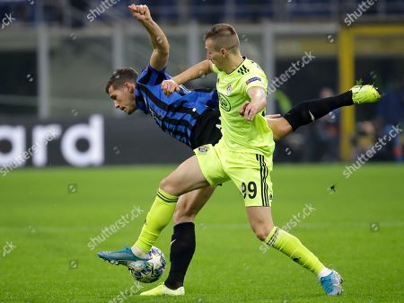 Dinamo Zagreb's Mislav Orsic, right, challenges Atalanta's Remo Freuler, left, during the Champions League group C soccer match between Atalanta and Dinamo Zagreb at the San Siro stadium in Milan, Italy