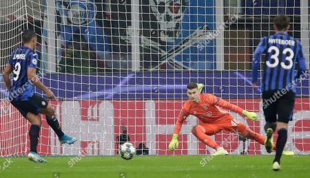Atalanta's Luis Muriel, left, scores a penalty kick past Dinamo Zagreb's goalkeeper Dominik Livakovic, center, during the Champions League group C soccer match between Atalanta and Dinamo Zagreb at the San Siro stadium in Milan, Italy