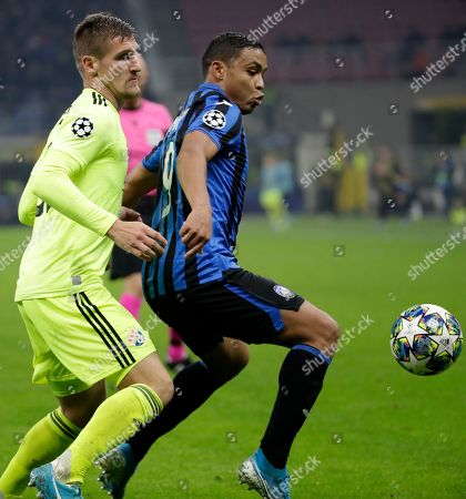Dinamo Zagreb's Emir Dilaver, left, challenges Atalanta's Luis Muriel, right, during the Champions League group C soccer match between Atalanta and Dinamo Zagreb at the San Siro stadium in Milan, Italy