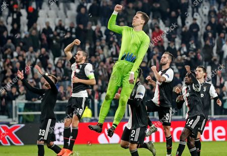 Juventus' goalkeeper Wojciech Szczesny jumps in the air, celebrating with his team after winning the Champions League group D soccer match between Juventus and Atletico Madrid at the Allianz stadium in Turin, Italy