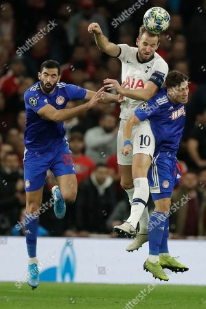 Tottenham's Harry Kane, centre, vies for the ball with Olympiakos' Yassine Meriah left, and Olympiakos' Kostas Tsimikas during the Champions League Group B soccer match between Tottenham Hotspur and Olympiakos at the Tottenham Hotspur Stadium in London