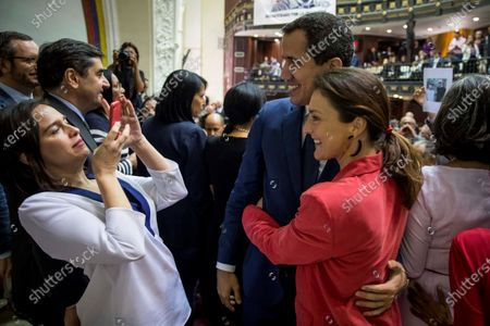 Stock Image of President of the National Assembly of Venezuela, Juan Guaido (C), hugs Valentina Martinez, Secretary of International Relations of the PP, while taking the photo Belen Hoyo, President of the National Electoral Committee of the PP, after taking part in the session of the day in the Venezuelan National Assembly, in the hemicycle of sessions of the organization, after the event 'World parliamentary meeting for democracy', in Caracas, Venezuela, 26 November 2019. The intervention by surprise in the Venezuelan National Assembly (AN) of Spanish senator Javier Maroto and deputy Jose Ignacio Echaniz, both of the Popular Party (PP, right), unleashed a altercation between opposition and official deputies that ended in insults Among congressmen.