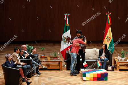 Bolivia's former President Evo Morales is hugged by a speaker during a dialogue with students and members of indigenous communities at Ollin Yoliztli Cultural Center in Mexico City, . Bolivia is struggling to stabilize after weeks of anti-government protests and violence in which at least 30 people have been killed. Former president Evo Morales resigned on Nov. 10 after an election that the opposition said was rigged