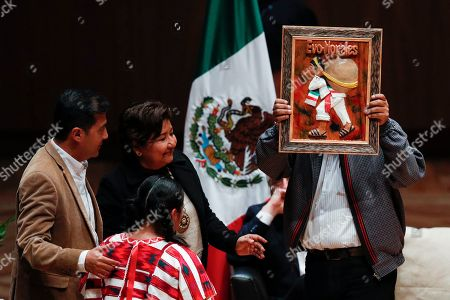 Bolivia's former President Evo Morales, right, holds up a gift presented by members of an indigenous community, during a dialog with students and indigenous people at Ollin Yoliztli Cultural Center in Mexico City
