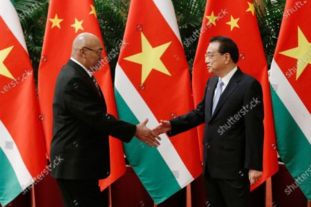 President of Suriname Desi Bouterse (L) and Chinese Premier Li Keqiang (R) shake hands before a meeting at the Great Hall of the People in Beijing, China, 27 November 2019.