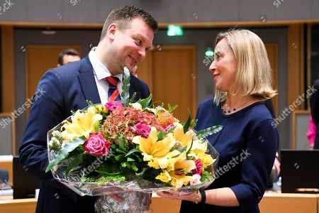 European Union Foreign Policy chief Federica Mogherini (R) receives flowers from Finnish Minister for Development Cooperation and Foreign Trade, Ville Skinnari (L) as she attends her last council meeting the EU Foreign Affairs Council (development) meeting