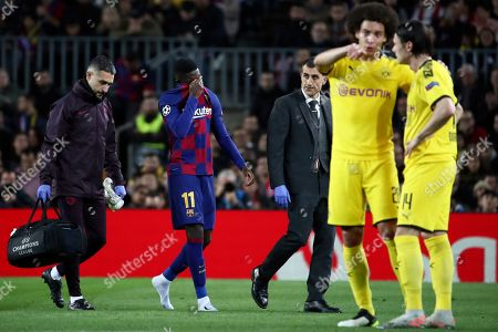 Barcelona's Ousmane Dembele, 2nd left, leaves the field after getting injured during a Champions League group F soccer match between Barcelona and Borussia Dortmund at the Camp Nou stadium in Barcelona, Spain