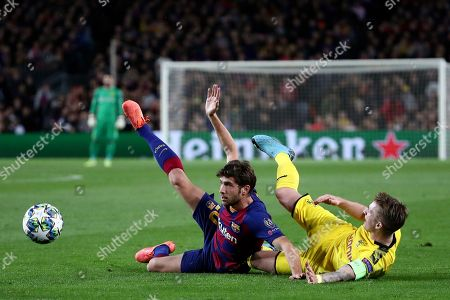Barcelona's Sergi Roberto falls down with Dortmund's Marco Reus, right, during a Champions League group F soccer match between Barcelona and Borussia Dortmund at the Camp Nou stadium in Barcelona, Spain