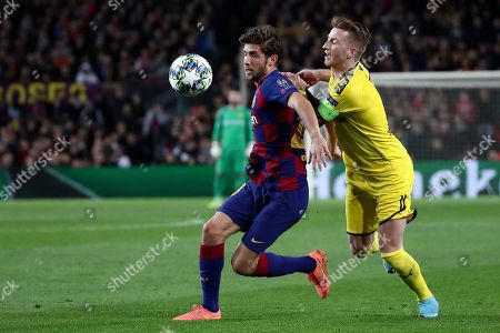 Barcelona's Sergi Roberto vies for the ball with Dortmund's Marco Reus, right, during a Champions League group F soccer match between Barcelona and Borussia Dortmund at the Camp Nou stadium in Barcelona, Spain