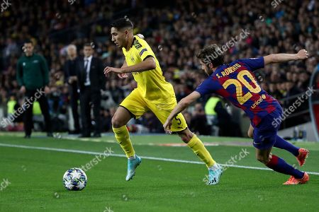 Dortmund's Achraf Hakimi runs with the ball away from Barcelona's Sergi Roberto, right, during a Champions League group F soccer match between Barcelona and Borussia Dortmund at the Camp Nou stadium in Barcelona, Spain