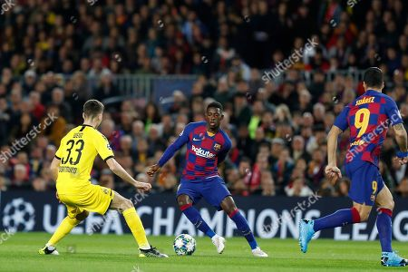 Barcelona's Ousmane Dembele, centre, controls the ball in front of Dortmund's Julian Weigl during a Champions League soccer match Group F between Barcelona and Dortmund at the Camp Nou stadium in Barcelona, Spain