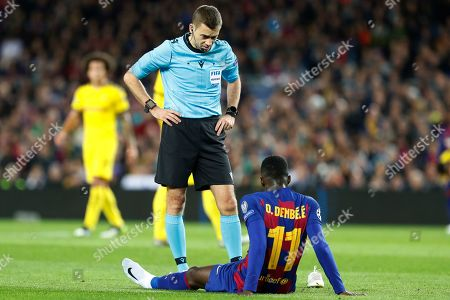 The referee speaks with Barcelona's Ousmane Dembele who had to be substituted after getting injured during a Champions League soccer match Group F between Barcelona and Dortmund at the Camp Nou stadium in Barcelona, Spain