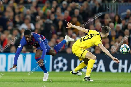 Barcelona's Ousmane Dembele, left, falls by Dortmund's Julian Weigl during a Champions League soccer match Group F between Barcelona and Dortmund at the Camp Nou stadium in Barcelona, Spain