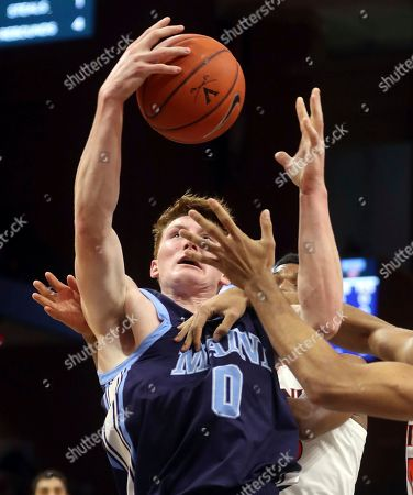 Maine forward Andrew Fleming (0) gets pressured from the Virginia defenders during an NCAA college basketball game in Charlottesville, Va