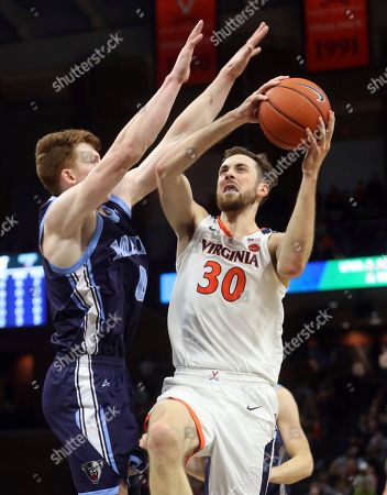 Virginia forward Jay Huff (30) shoots next to Maine forward Andrew Fleming (0) during an NCAA college basketball game in Charlottesville, Va., . Virginia won 46-26