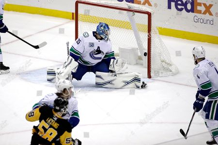 A shot by Pittsburgh Penguins' Kris Letang (58) gets past Vancouver Canucks goaltender Thatcher Demko for a goal during the third period of an NHL hockey game in Pittsburgh, . The Penguins won 8-6