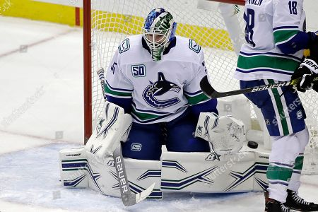 A shot by Pittsburgh Penguins' Kris Letang gets past the glove hand of Vancouver Canucks goaltender Thatcher Demko for a goal during the third period of an NHL hockey game in Pittsburgh, . The Penguins won 8-6