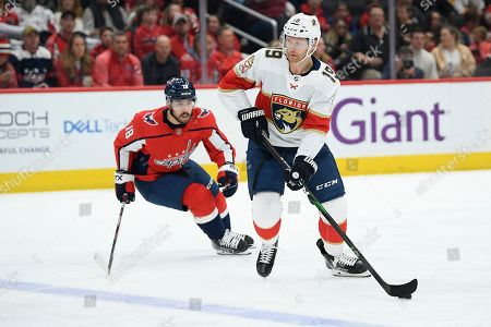 Florida Panthers defenseman Mike Matheson (19) skates with the puck next to Washington Capitals center Chandler Stephenson (18) during the first period of an NHL hockey game, in Washington