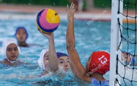 Philippines' Carla Beatriz Grabador, center, aims the ball towards the goal against Khemasiri Sirivejjabandh, right, during the 1st round robin match against Philippines at the 30th South East Asian Games at the New Clark City, Tarlac province, northern Philippines on . Thailand won 32-5