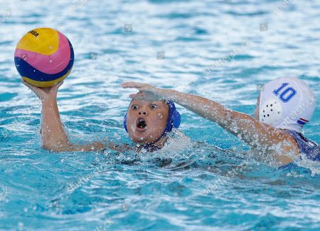 Philippines' Gabriella Sicat, left, passes the ball during their 1st round robin water polo women's match against Thailand at the 30th South East Asian Games at the New Clark City, Tarlac province, northern Philippines on . Thailand won 32-5