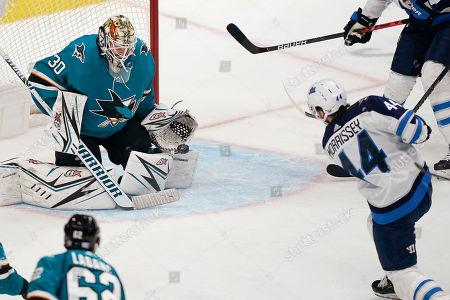 San Jose Sharks goaltender Aaron Dell (30) blocks a shot by Winnipeg Jets defenseman Josh Morrissey (44) during the third period of an NHL hockey game in San Jose, Calif., . The Jets won 5-1