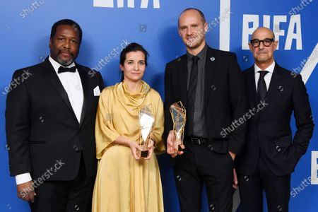 Waad Al-Kateab, Edward Watts - Best British Independent Film, Best Director and Best Documentary - For Sama, holding the BIFA trophy, created by Swarovski, presented by Stanley Tucci and Wendell Pierce