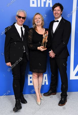 Zara Balfour, Marcus Stephenson, Mark Hakansson - The Discovery Award - Children Of The Snow Land holding the BIFA trophy, created by Swarovski, accompanied by Elliot Grove\
