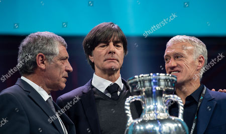 Joachim Loew, Head Coach of Germany looks at the trophy alongside Fernando Santos, Head Coach of Portugal and Didier Deschamps, Head Coach of France
