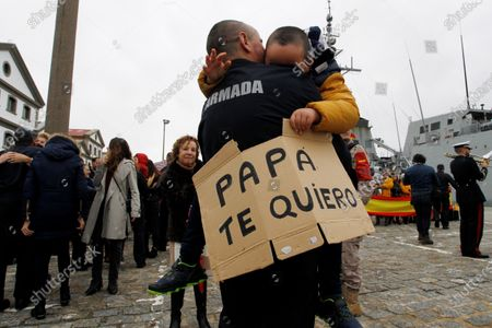 Stock Photo of A crew member of the frigate Mendez Nunez holds his son who carries a banner that reads 'Daddy, I love you', upon the frigate's arrival to Ferrol, Spain, 28 November 2019. Military frigate Mendez Nunez returned back home after a circumnavigation that started in April 2019 on the occasion of the 500 anniversary of the first circumnavigation by Juan Sebastian Elcano and Ferdinand Magellan.