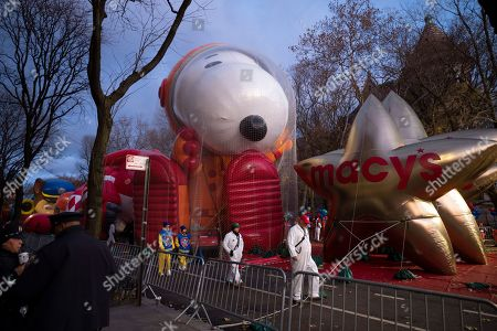 The Snoopy the Astronaut, center, and Macy's Stars balloons are held down by protective netting before the start of the Macy's Thanksgiving Day Parade, in New York