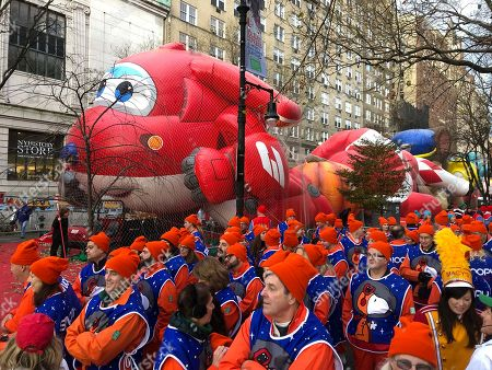 The Snoopy balloon handlers wait for the start of the Macy's Thanksgiving Day Parade, in New York