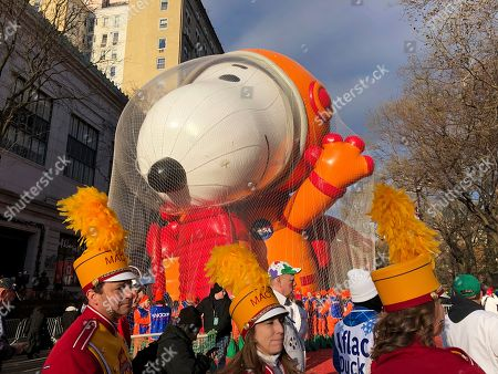 Participants in the Macy's Thanksgiving Day Parade assemble in front of the Snoopy balloon before the start of the parade, in New York