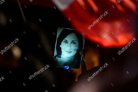 A protester holds up a picture of murdered reporter Daphne Caruana Galizia on the fourth day of a demonstration outside Malta's prime minister's office in Valletta, Malta, . On Wednesday Maltese police arrested Prime Minister Joseph Muscat's former chief of staff Keith Schembri for questioning as a person of interest in the murder of the journalist