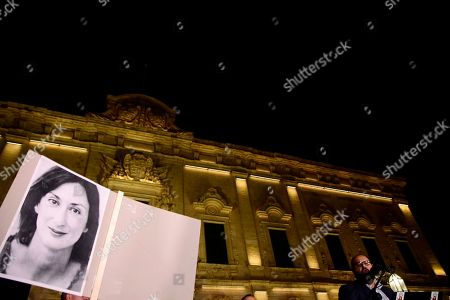 A protester holds up a picture of murdered reporter Daphne Caruana Galizia on the second day of a demonstration outside Malta's prime minister's office in Valletta, Malta, early . On Wednesday, Nov. 28, 2019 Maltese police arrested Prime Minister Joseph Muscat's former chief of staff Keith Schembri for questioning as a person of interest in the murder of the journalist
