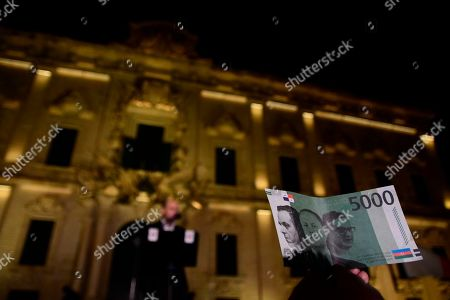 A protester holds up a fake banknote showing the faces of Malta's Prime Minister Joseph Muscat, center, Muscat's chief of staff Keith Schembri, left, and Tourism Minister Konrad Mizzi, on the second day of a demonstration outside Malta's prime minister's office in Valletta, Malta, early . On Wednesday, Nov. 28, 2019 Maltese police arrested Prime Minister Joseph Muscat's former chief of staff Schembri for questioning as a person of interest in the murder of the journalist Daphne Caruana Galizia