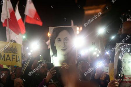 Protestors hold up a pictures of slain journalist Daphne Caruana Galizia during a demonstration outside Malta's prime minister's office in Valletta, Malta, . On Wednesday, Nov. 27, 2019 Maltese police arrested Prime Minister Joseph Muscat's former chief of staff Keith Schembri for questioning as a person of interest in the murder of journalist Daphne Caruana Galizia