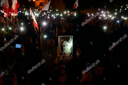 Protestors hold up a pictures of slain journalist Daphne Caruana Galizia during a demonstration outside Malta's prime minister's office in Valletta, Malta, . On Wednesday, Nov. 27, 2019 Maltese police arrested Prime Minister Joseph Muscat's former chief of staff Keith Schembri for questioning as a person of interest in the murder of Galizia
